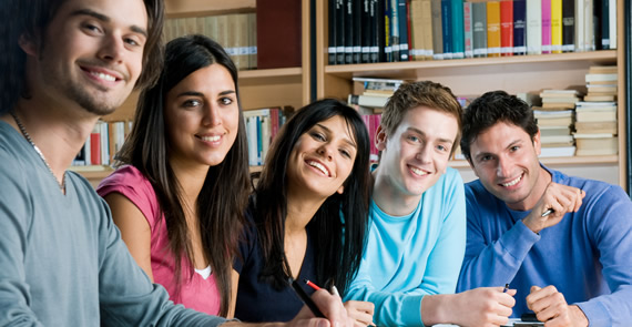 college students sitting at table in library