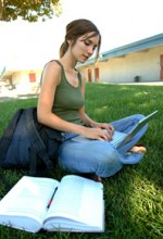 college girl sitting on grass with laptop