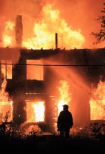 fireman watching structure burning